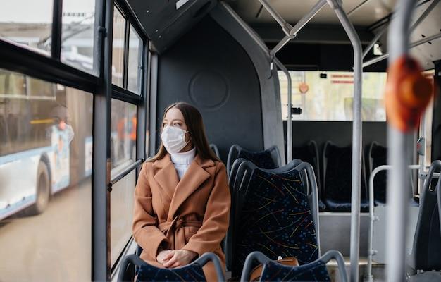 Jonge vrouw in een masker maakt gebruik van het openbaar vervoer