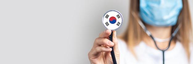 Jonge vrouw in een medisch masker houdt een stethoscoop met de vlag van de republiek korea