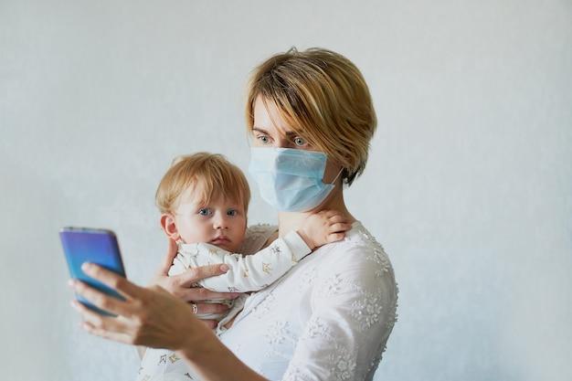Jonge vrouw in een medisch masker met een baby in haar armen roept op de telefoon