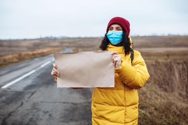Jonge vrouw in een medisch masker met gele jas en rode hoed staat met een blanco posterpapier aan de kant van een lege weg.