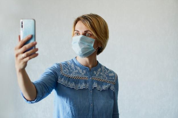 Jonge vrouw in een medisch masker roept op de telefoon