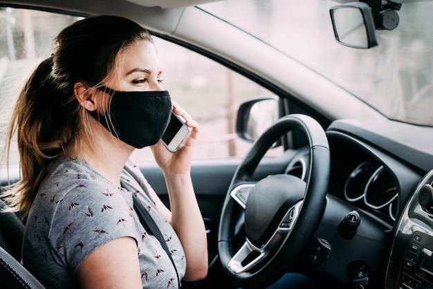 Jonge vrouw in een medisch masker zitten in een auto met het stuur links en praten over de telefoon
