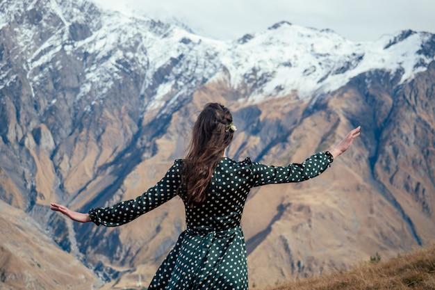 Jonge vrouw in een mooie jurk in de bergen uitzicht vanaf de achterkant