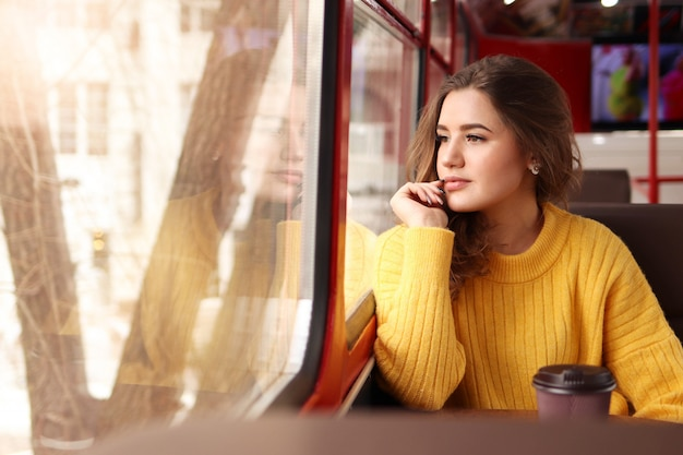 Jonge vrouw in een mosterd trui zit in een café en kijkt uit het raam