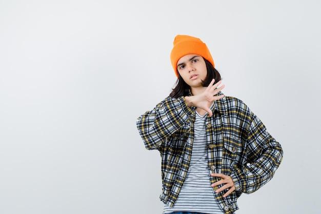 Jonge vrouw in een oranje hoed met geruit hemd die hand in de buurt van het gezicht houdt en weemoedig kijkt