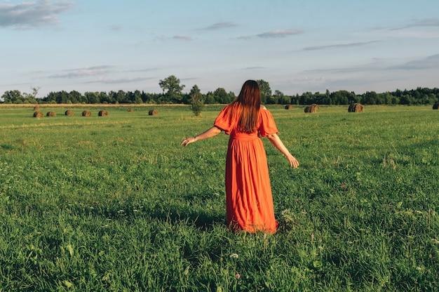 Jonge vrouw in een oranje jurk poseren in de natuur