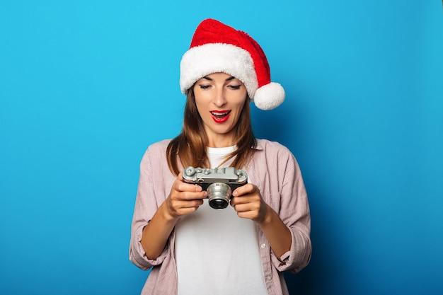 Jonge vrouw in een overhemd dat een hoed van de kerstman draagt