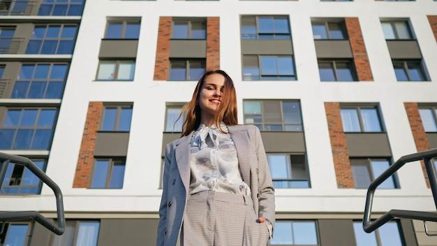 Jonge vrouw in een pak daalt de trap af op de achtergrond van het gebouw