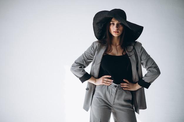 Jonge vrouw in een pak dat een hoed draagt