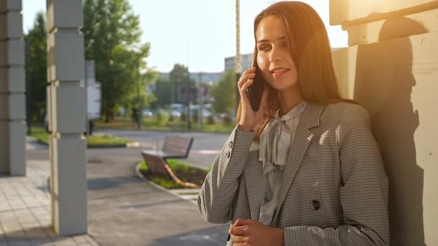 Jonge vrouw in een pak die aan de telefoon praat terwijl ze op straat staat