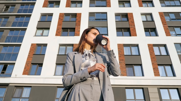 Jonge vrouw in een pak drinkt koffie uit een plastic beker op de achtergrond van een gebouw op een zonnige dag