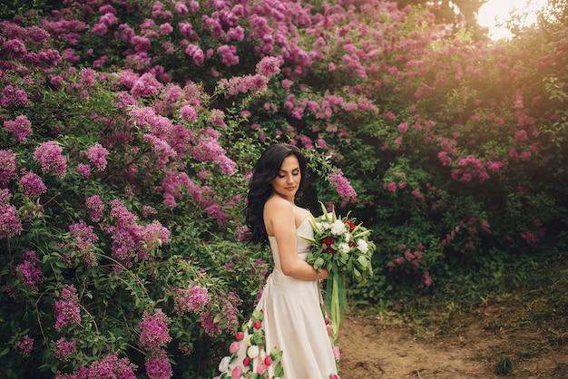 Jonge vrouw in een pioenroos jurk staat in een bloeiende lila tuin bij zonsondergang