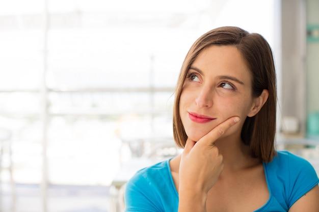 Jonge vrouw in een restaurant denken