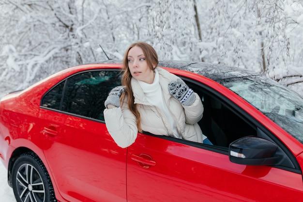 Jonge vrouw in een rode auto op de achtergrond van een winterbos