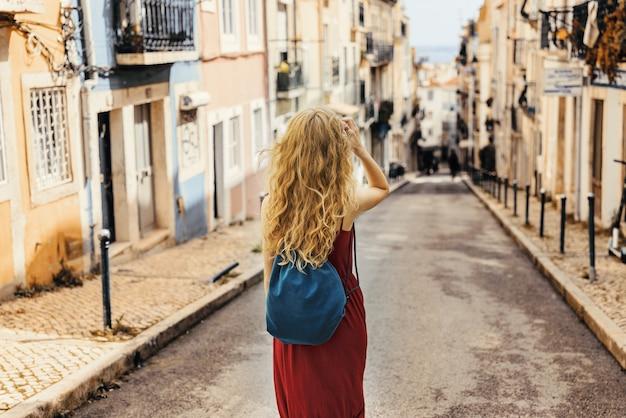 Jonge vrouw in een rode jurk loopt door een weg omringd door gebouwen in het zonlicht
