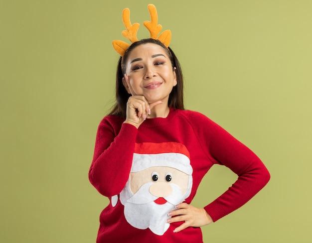 Jonge vrouw in een rode kersttrui met een grappige rand met hertenhoorns die vrolijk, gelukkig en positief glimlachen over de groene muur