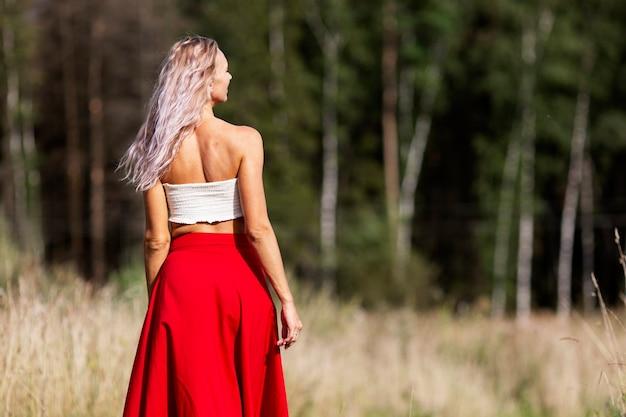 Jonge vrouw in een rode rok in het veld