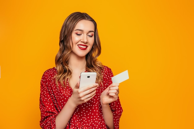 Jonge vrouw in een rode zomerjurk heeft een mobiele telefoon en een creditcard in haar handen geïsoleerd op een oranje muur met mockup. meisje kijkt naar de telefoon en doet online aankopen