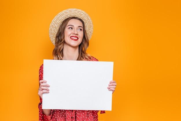 Jonge vrouw in een rode zomerjurk in een strooien hoed met een blanco vel papier geïsoleerd op een oranje achtergrond