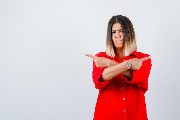 Jonge vrouw in een rood oversized shirt dat naar beide kanten wijst en aarzelend kijkt, vooraanzicht.