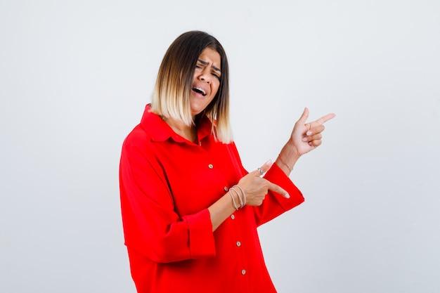 Jonge vrouw in een rood oversized shirt dat naar de rechterkant wijst en er energiek uitziet, vooraanzicht.