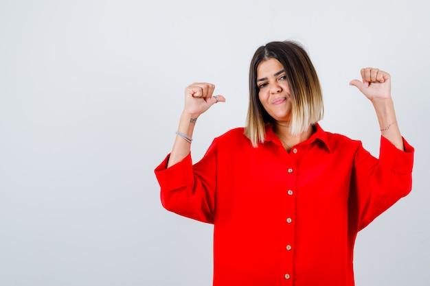 Jonge vrouw in een rood oversized shirt die duimen naar achteren wijst en er zelfverzekerd uitziet, vooraanzicht.