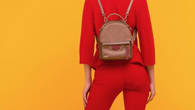 Jonge vrouw in een rood pak met een kleine rugzak