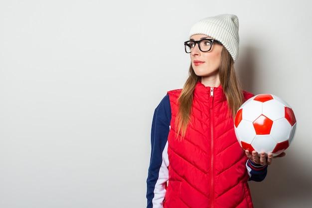 Jonge vrouw in een rood vest, hoed en bril houdt een voetbal en kijkt naar de zijkant