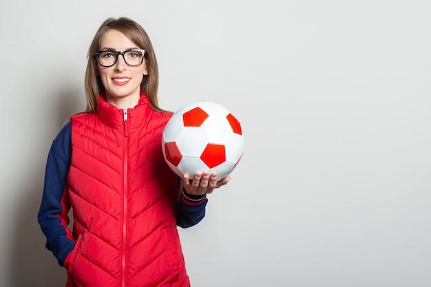 Jonge vrouw in een rood vest met een voetbalbal tegen een lichte muur