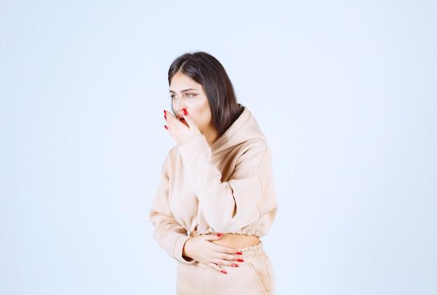 Jonge vrouw in een roze hoodie caughing en heeft keelpijn