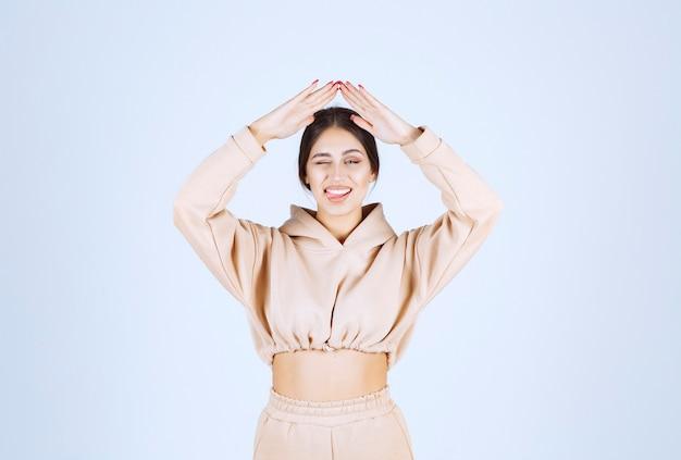 Jonge vrouw in een roze hoodie die dak boven haar hoofd maakt