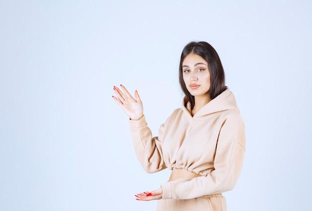 Jonge vrouw in een roze hoodie die de geschatte afmetingen van een object demonstreert