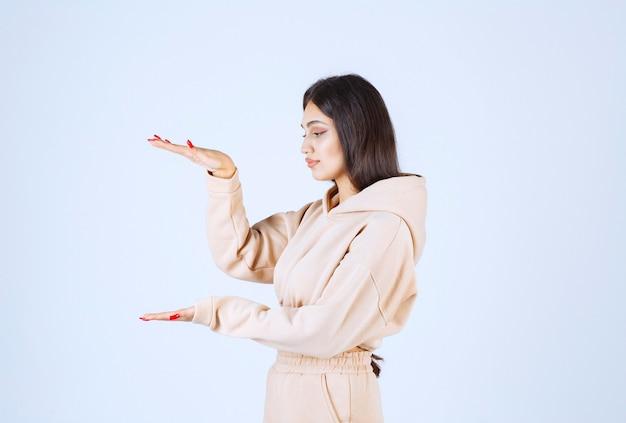 Jonge vrouw in een roze hoodie die de hoeveelheid of de grootte van een voorwerp toont