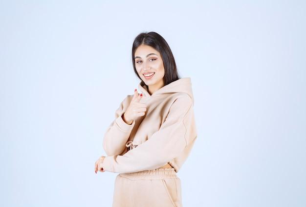 Jonge vrouw in een roze hoodie die de persoon voor haar richt