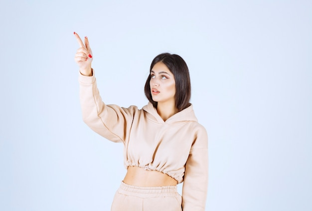 Jonge vrouw in een roze hoodie die ergens hierboven wijst