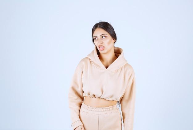 Jonge vrouw in een roze hoodie die haar tong uitzet
