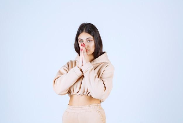 Jonge vrouw in een roze hoodie die handen verenigt en bidt