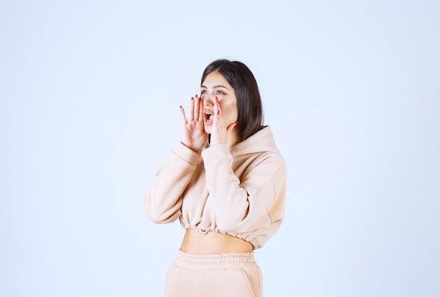 Jonge vrouw in een roze hoodie die hardop schiet Gratis Foto