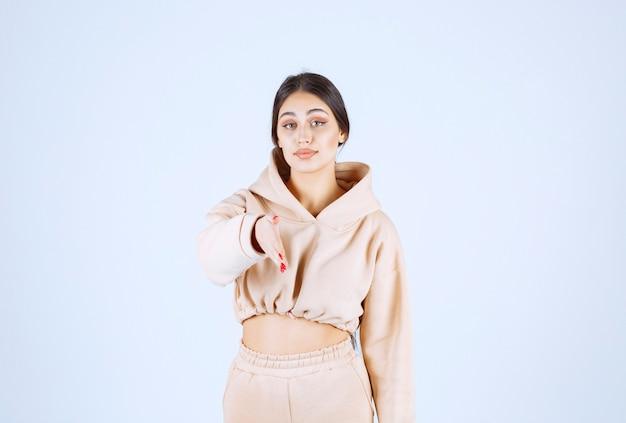 Jonge vrouw in een roze hoodie die iemand groet