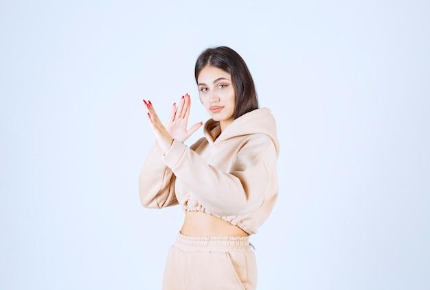 Jonge vrouw in een roze hoodie die iemand tegenhoudt