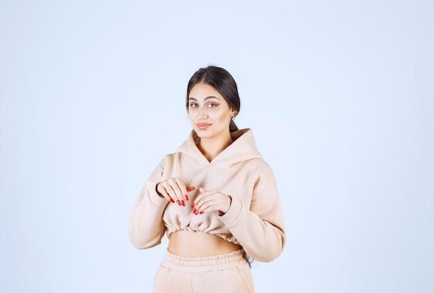 Jonge vrouw in een roze hoodie die konijnenpoten imiteert