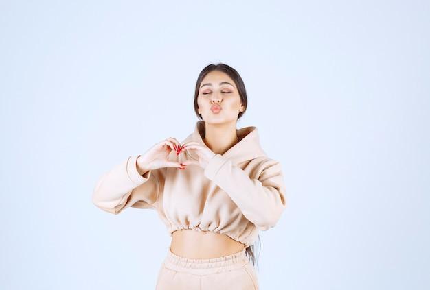 Jonge vrouw in een roze hoodie die mooie en oprechte poses geeft