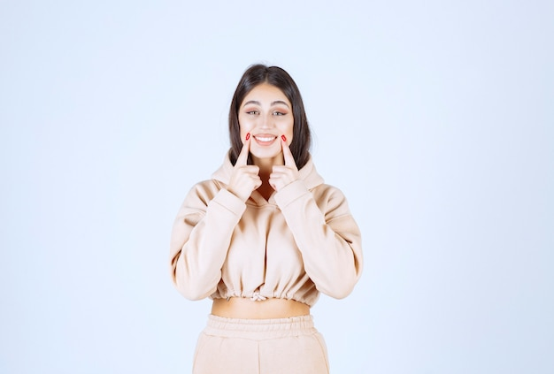 Jonge vrouw in een roze hoodie die op haar glimlach richt