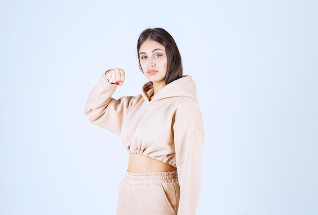 Jonge vrouw in een roze hoodie die sterk en krachtig voelt