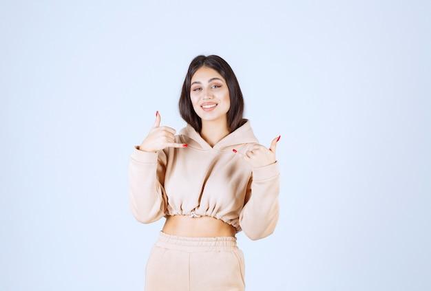Jonge vrouw in een roze hoodie die vraagt om te bellen