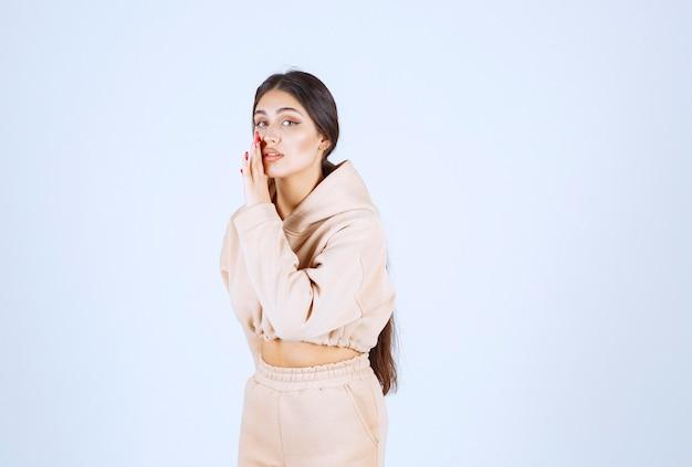 Jonge vrouw in een roze hoodie fluisteren en roddelen