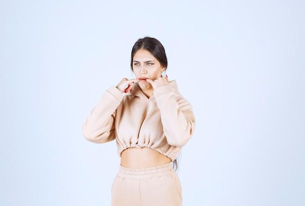 Jonge vrouw in een roze hoodie fluiten