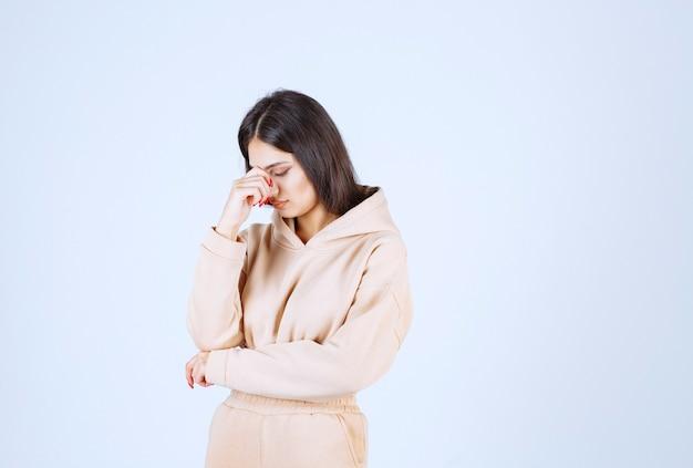 Jonge vrouw in een roze hoofd van de hoodieholding aangezien zij hoofdpijn heeft
