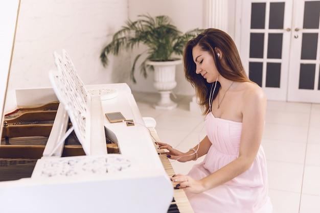 Jonge vrouw in een roze kleding die aan muziek in de telefoonhoofdtelefoons luistert en piano speelt