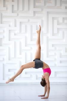 Jonge vrouw in een roze top op atletische training. studio opname.